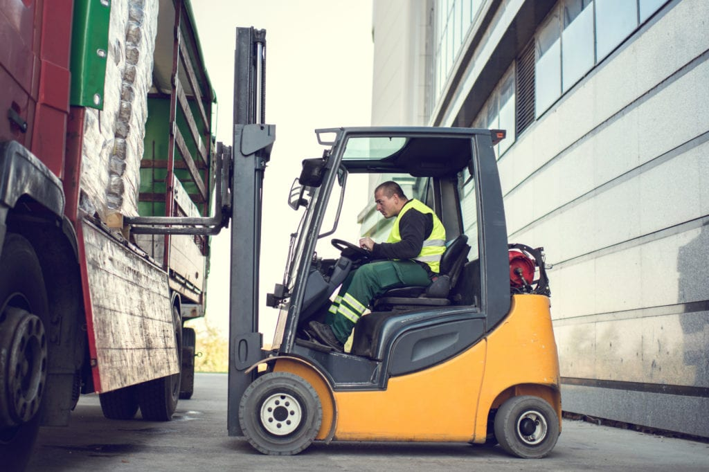 staffing agency insurance forklift operator loading crates into truck