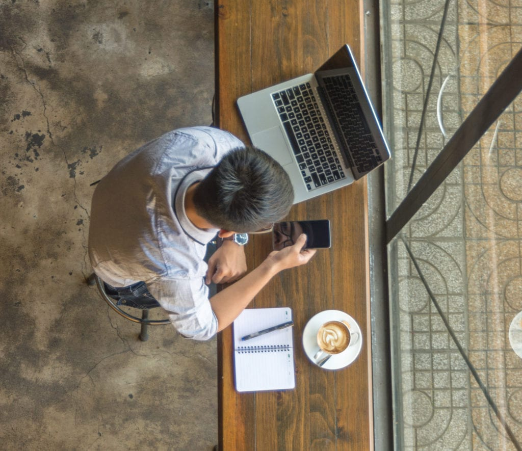 Cyber liability insurance data breach. Man in coffee shop with laptop and phone.
