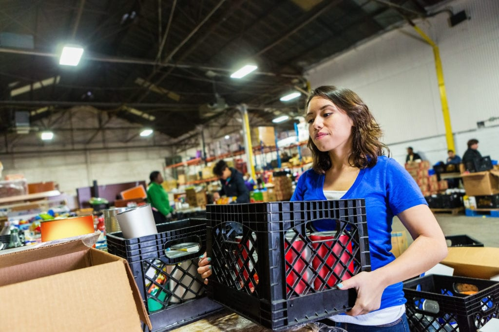Social services insurance property, a volunteer organizing donated items inside a warehouse.