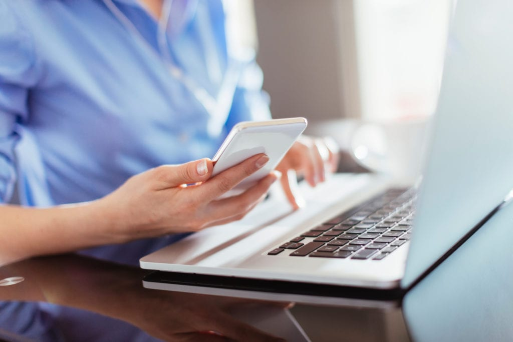 IT insurance cyber liability insurance. Businesswoman typing on smart phone.
