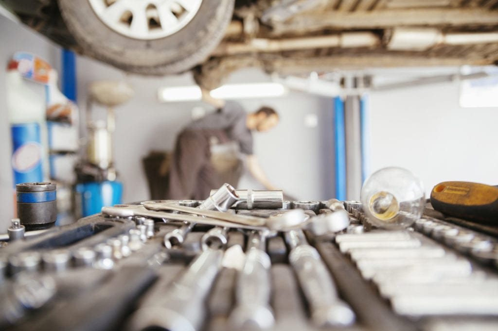 Garage insurance other insurance coverages. Close up of tools with car on lift in auto repair garage.