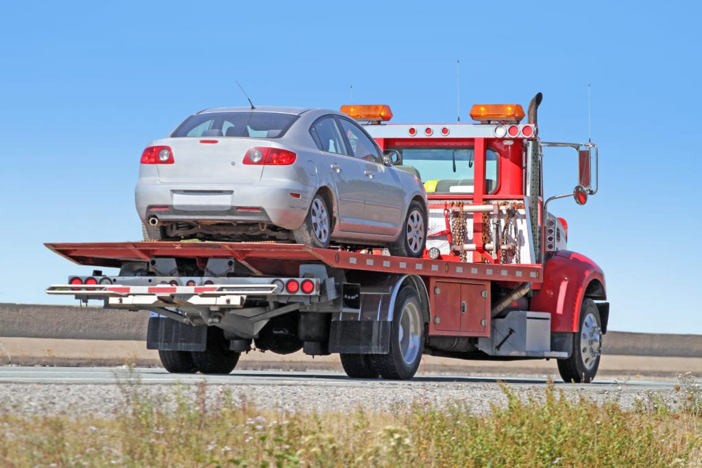 Garage insurance tow truck towing insurance. View or rear quarter of a red tilt bed tow truck on a highway carrying a gray sedan.