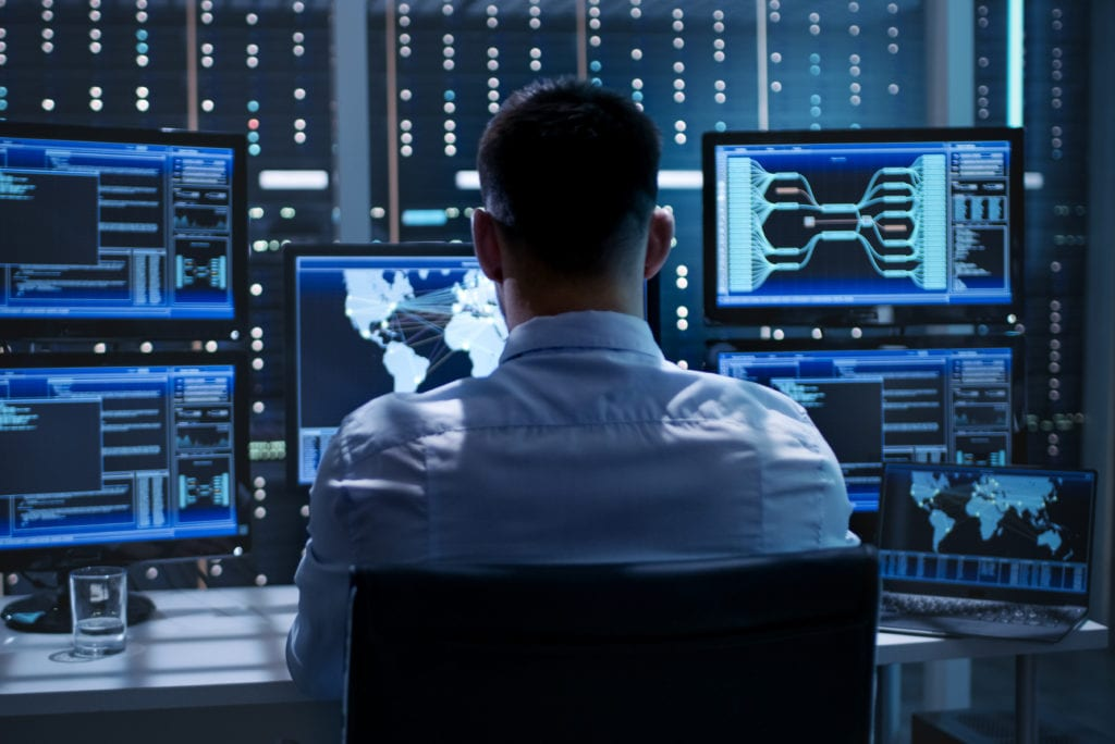 technology insurance professional liability coverage. System security specialist working at system control center.