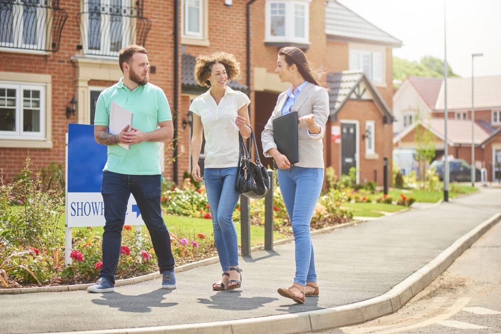 Property management insurance general liability. A property manager shows a couple a townhouse.