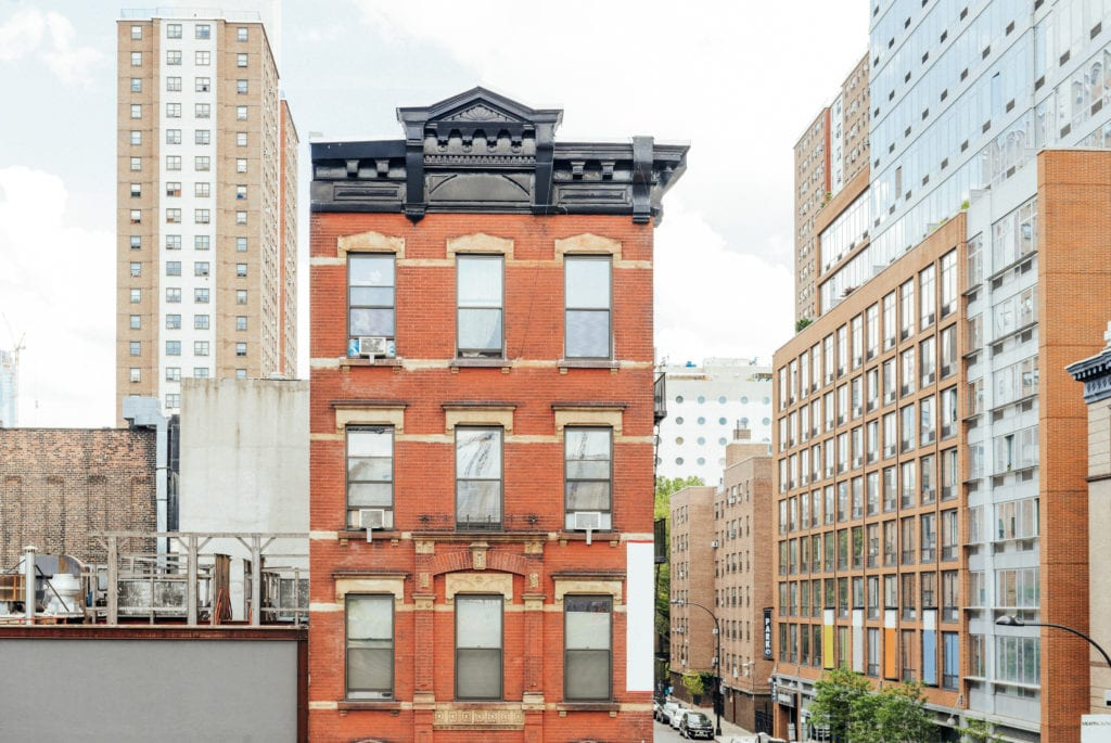 Property Management Insurance other coverages. Color photograph of residential buildings with commercial space in Manhattan.