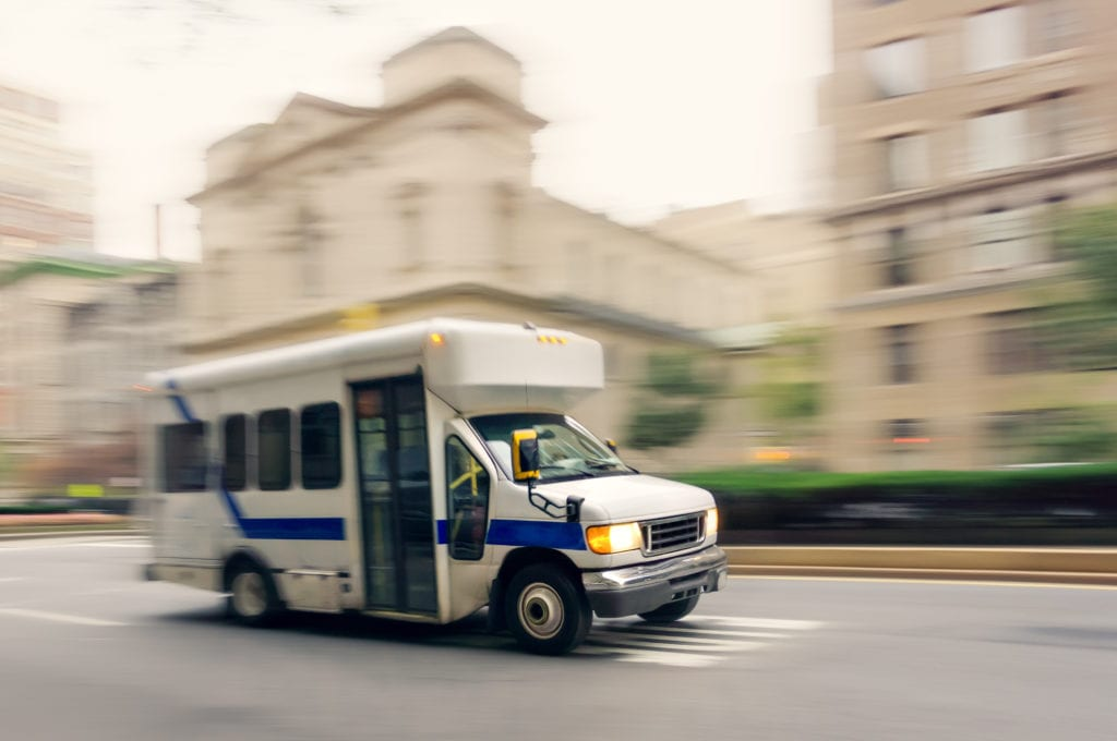 Business auto insurance for assisted living facilities, a small white bus with a blue stripe carries residents on a city street with motion blur background.