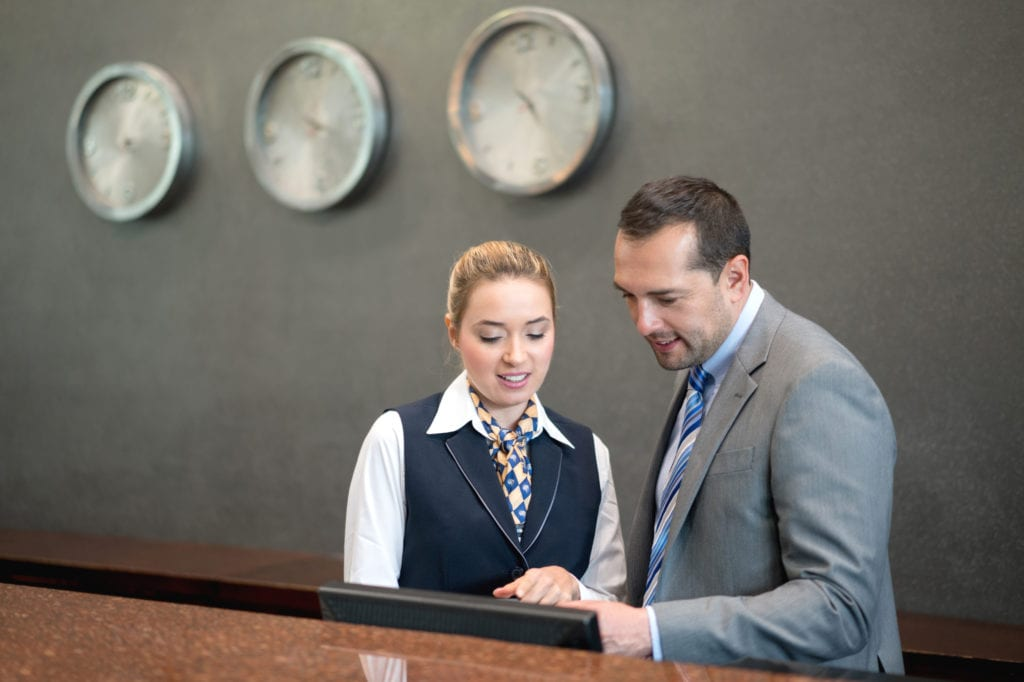 Hotel insurance workers compensation. A male hotel manager in gray suit talks to a woman working at the front desk.
