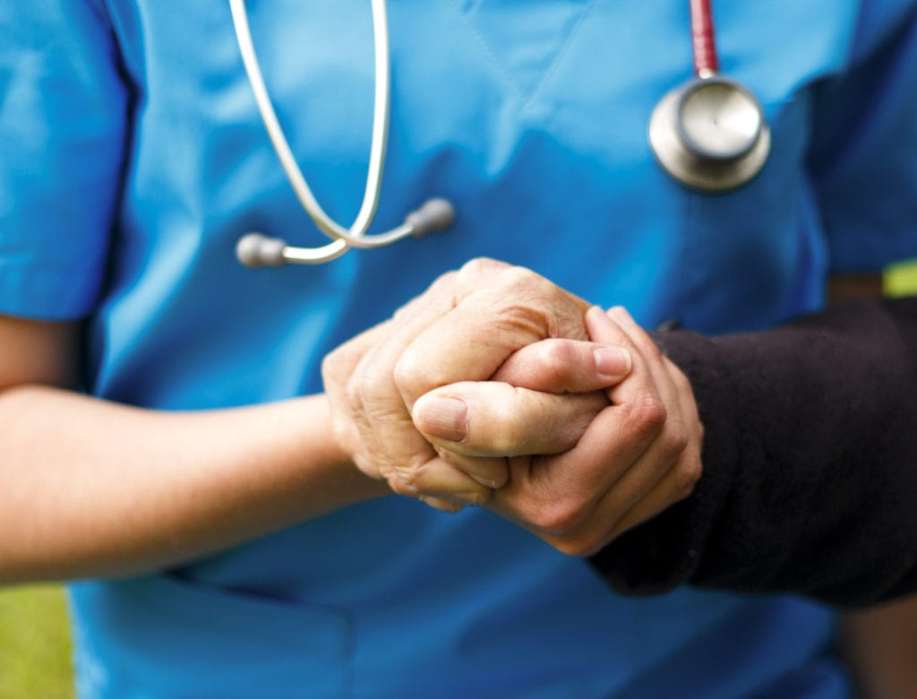 Professional liability insurance for assisted living facilities, a doctor in blue scrubs helps an older resident to stand.