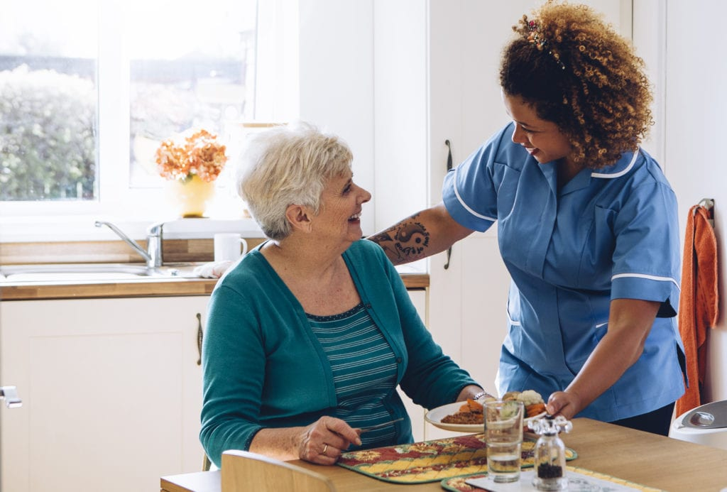 Workers compensation insurance for assisted living facilities, worker helping a woman at kitchen table, serving her a meal.