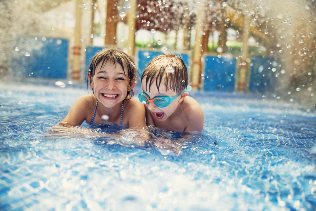 Motel insurance liability coverage. Two young children smiling and playing in motel pool.