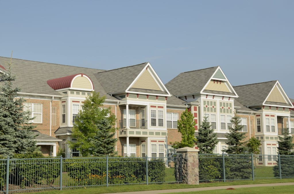 Property insurance for assisted living facilities, exterior view of two story assisted living complex with tan brick walls and brown shingled roof.