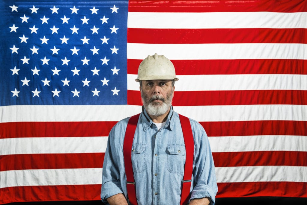 DBA insurance benefits, a bearded construction worker in white hat and red suspenders stands in front of an American flag.