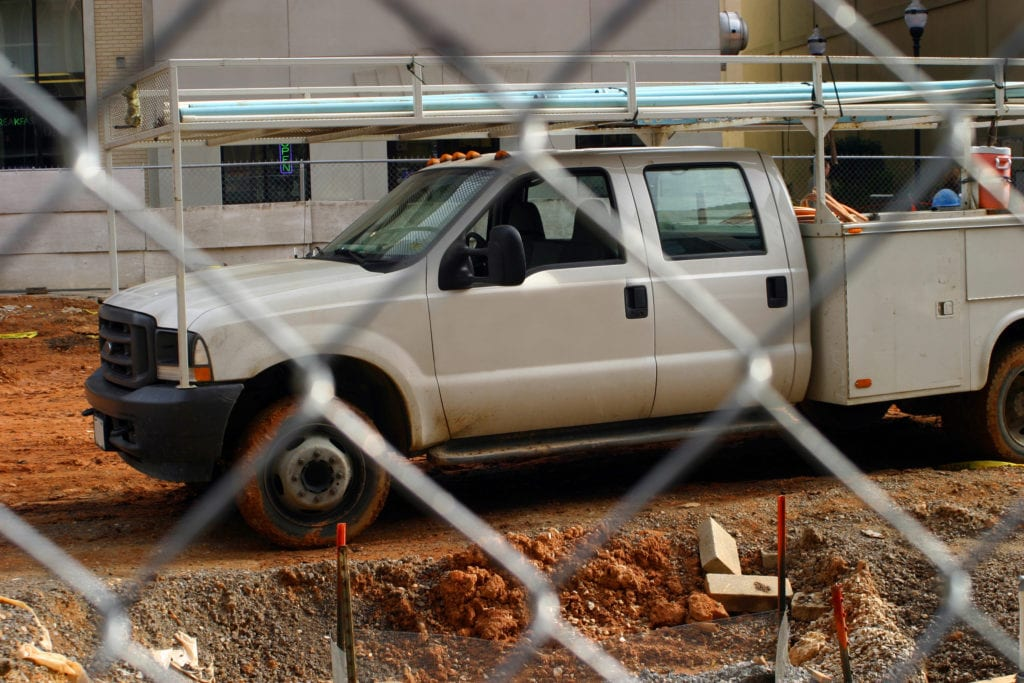 Auto insurance for framing contractors, white dually construction pickup with wheels rimmed in red mud on building site.