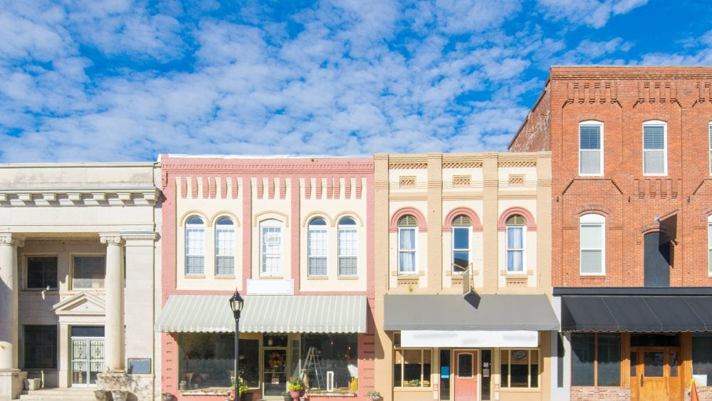Property valuation replacement cost actual cash value, four multi colored two and three story brick storefronts on a main street in America.