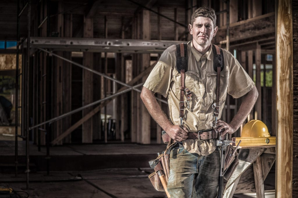 Workers compensation for framing contractors, sweaty carpenter standing in front of partially framed house.