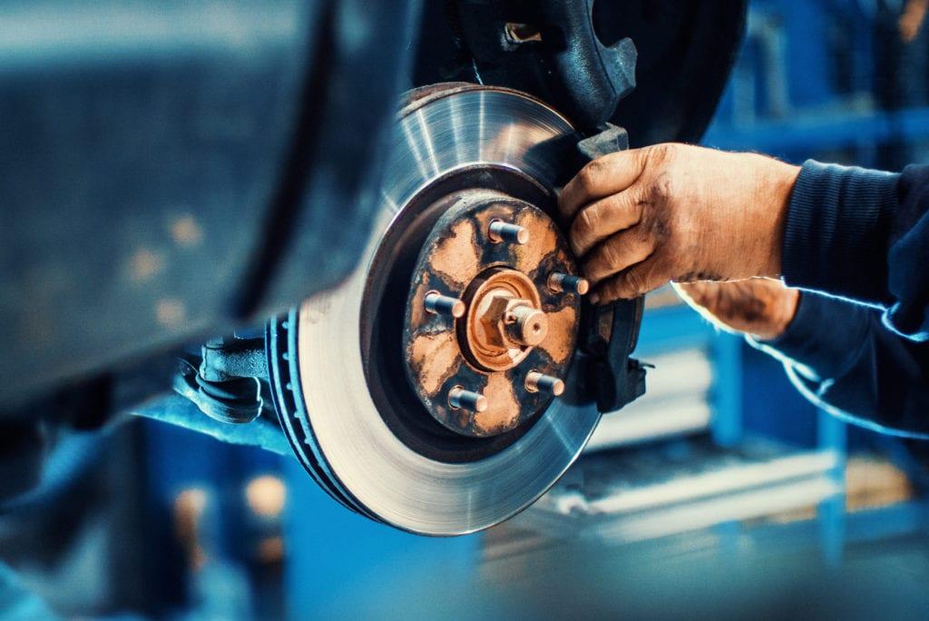 AutoZone ProVantage garage insurance program, mechanic replacing disc brake pads.
