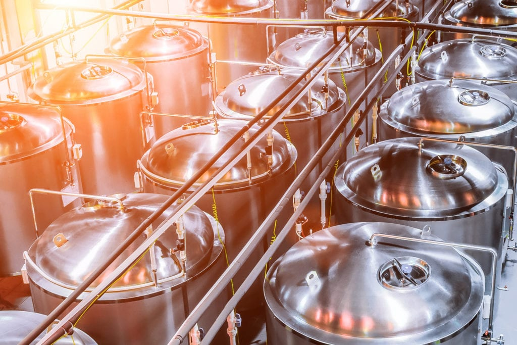 Craft brewery insurance equipment breakdown, stainless steel tanks in rows in a brewery.