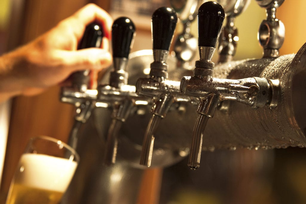 Craft brewery liability insurance, a barman fills a beer glass from a row of stainless steel taps, pipes dripping with condensation.