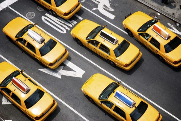 Public auto minimum liability limits, yellow taxi cabs make their way down the street of Broadway in New York City.
