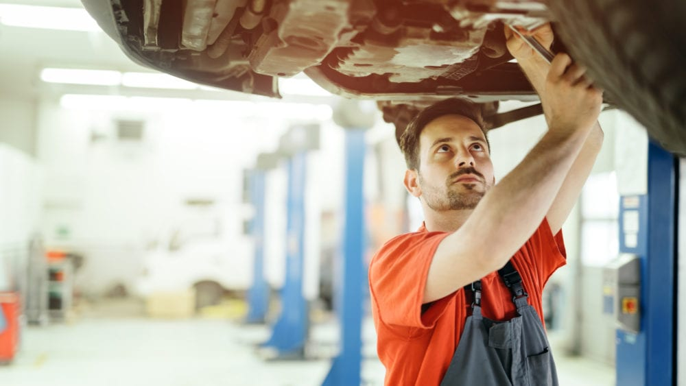 Free vehicle recall lookup tool, mechanic working below an automobile on a lift.