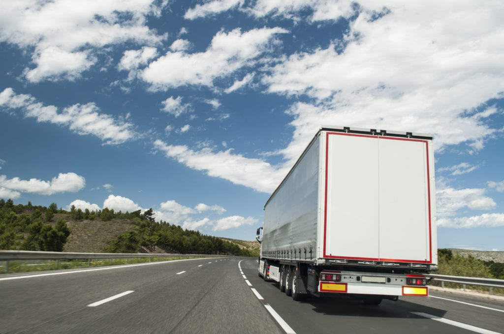 Commercial truck insurance other auto coverages, a white semi truck and trailer on the highway as seen from the rear.