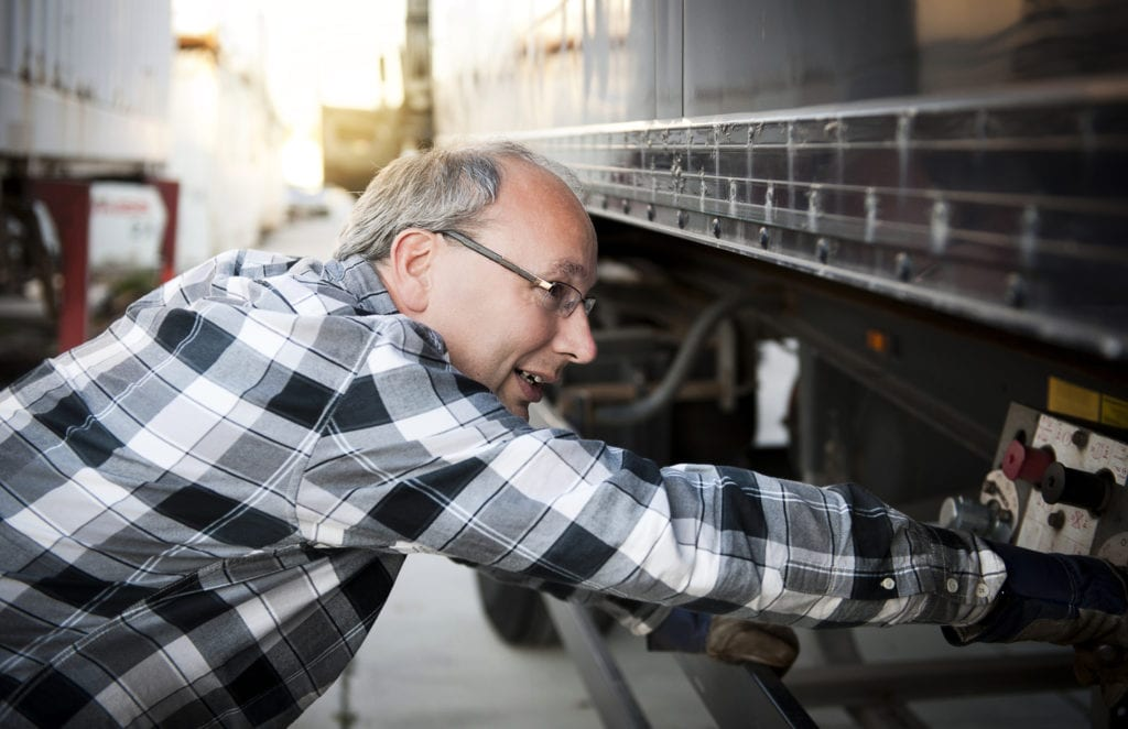 Commercial truck insurance workers compensation, truck driver checking trailer, ensuring all is properly hooked up.