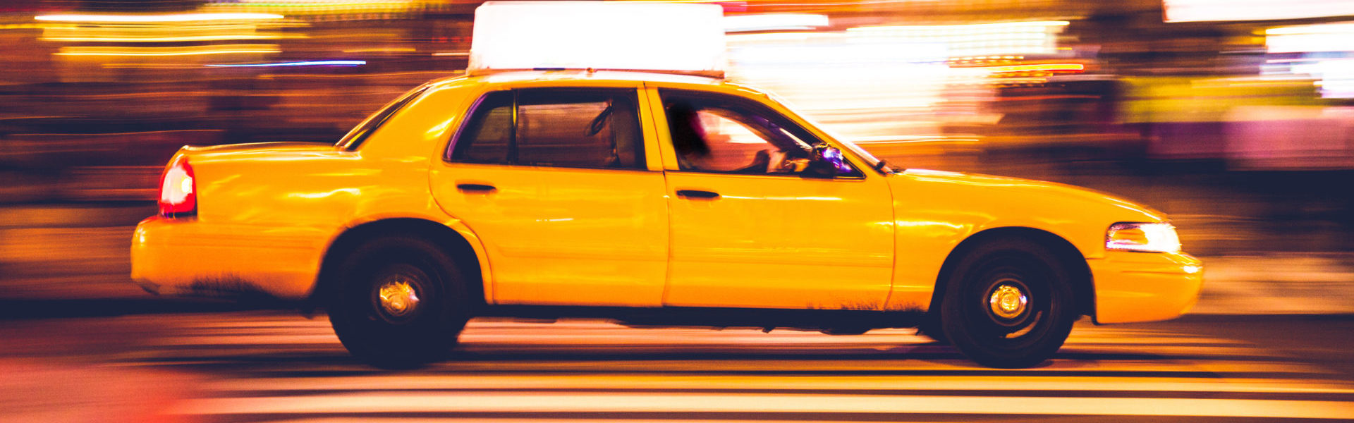 Livery insurance taxi, a yellow cab in New York with motion blur background.