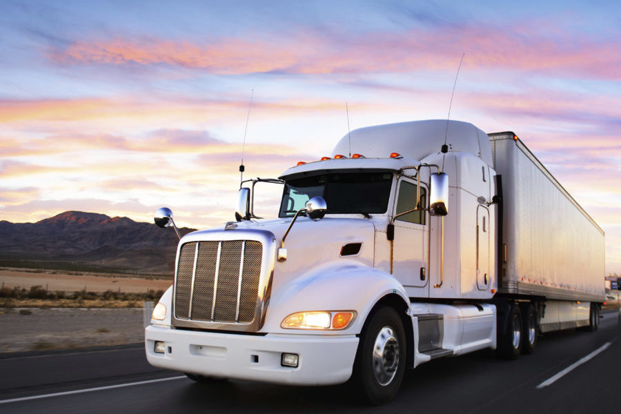 Truck insurance, white tractor and trailer on desert road at sunset.