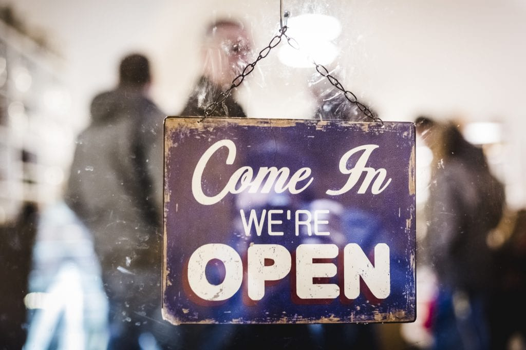 """Commercial Insurance Bank Referral, blue sign hanging in glass door saying, """"Come in. We're open."""""""