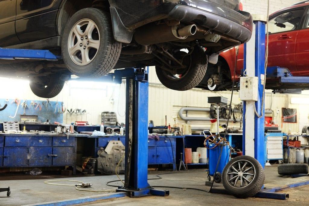Handling common hazardous substances auto garage, two vehicles on lifts in repair shop.
