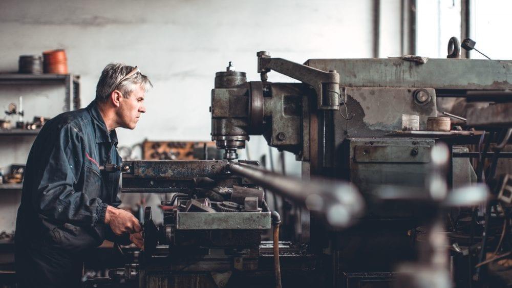 Virginia Manufacturers Association insurance program, machinist working on large milling machine.