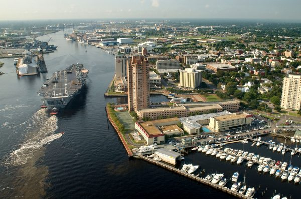 Aerial view of tug boats guiding USS Harry S Truman up the Elizabeth River past marina and tall hotels.