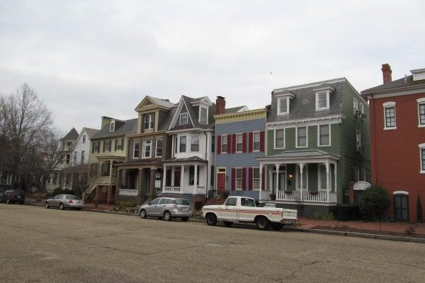 Residential street of downtown Portsmouth, VA, lined with multi colored victorian style townhomes.