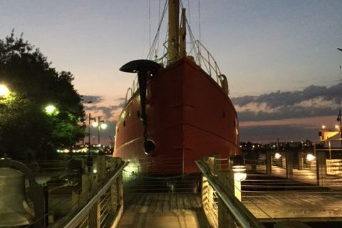 Lightship Portsmouth at evening, dramatic shot from dock facing red bow.