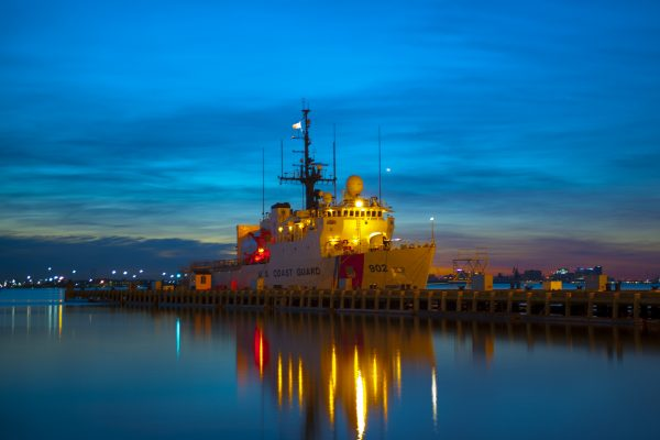 Coast Guard Cutter Tampa, homeport in Portsmouth, Va., shown docked against royal blue sky during sunrise.