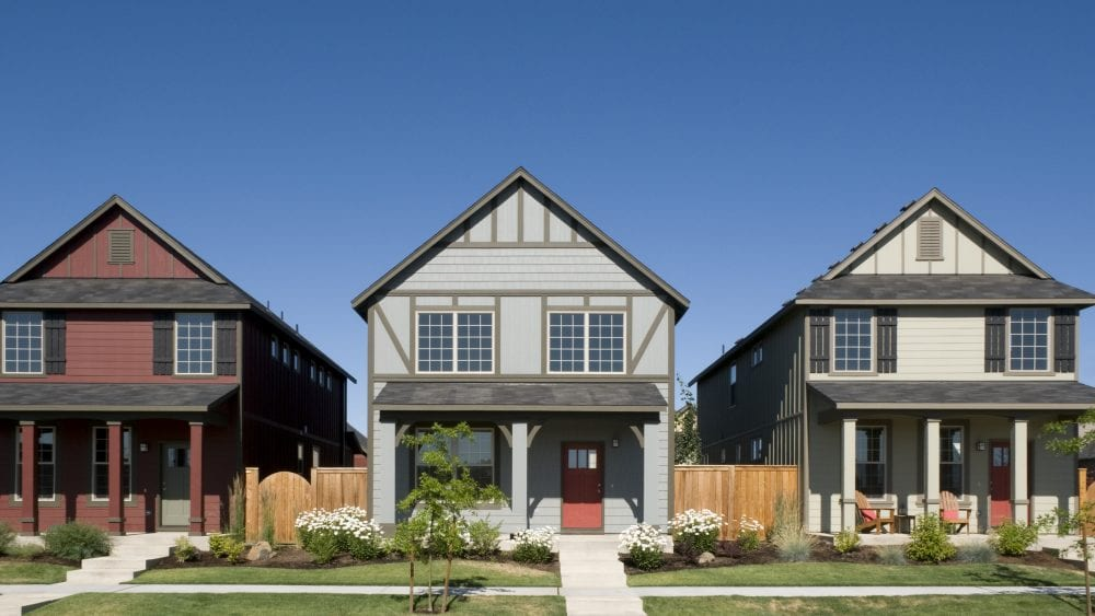 Homeowners insurance deductible, row of three similar houses on a neighborhood street.