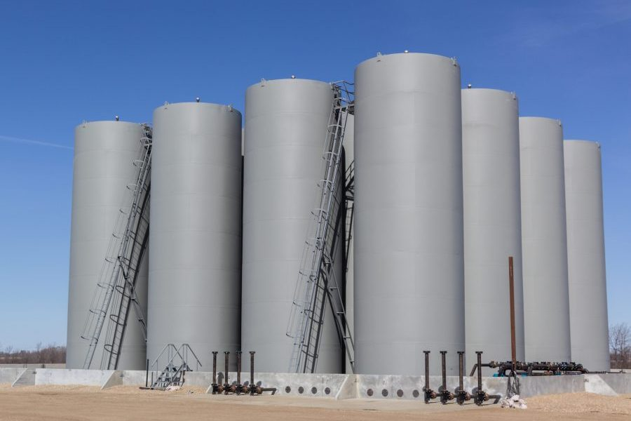 Insurance for fuel oil dealers property inland marine, grid of sixteen gray vertical storage tanks, tank farm.