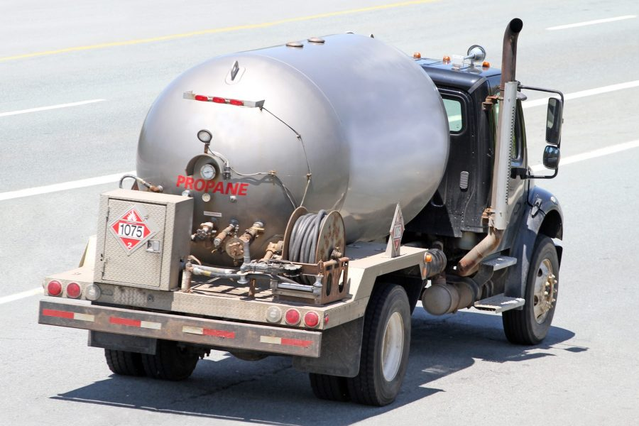 Insurance for propane dealers business auto, rear view of silver tank propane delivery truck on highway.