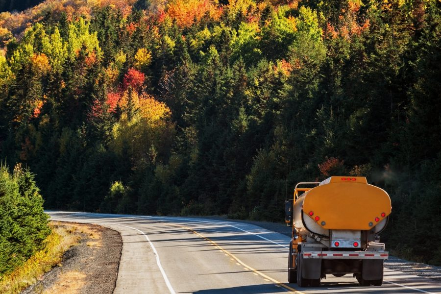 Insurance for propane dealers fueling our clients, fuel oil truck on mountain highway, trees in background in autumn colors.