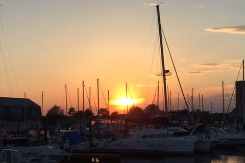 Sunset over a harbor with small craft and sailboats in Portsmouth, VA.