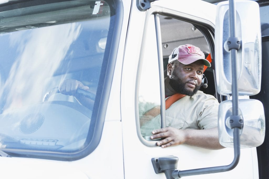 Insurance for propane dealers workers compensation, truck driver looking in rearview mirrors as he backs up truck.