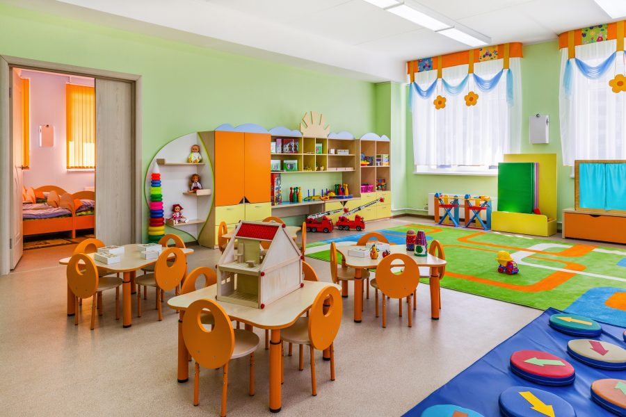 Childcare insurance, property coverage, a neat, colorful daycare room with tiny orange tables, green carpets, and nap room in background.