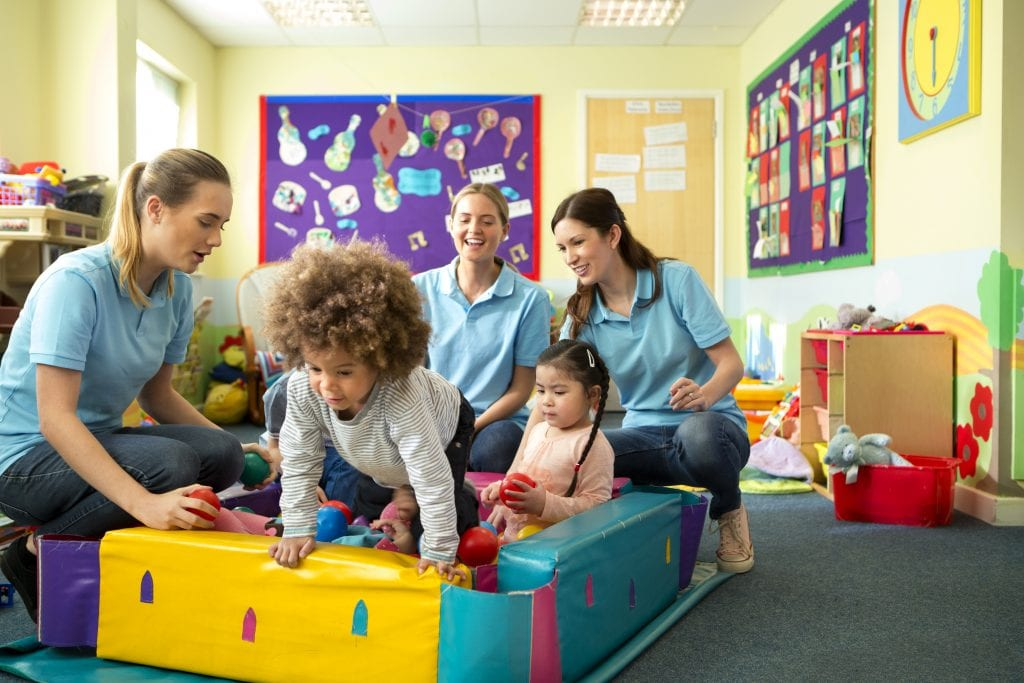 Daycare insurance for employee benefits, childcare workers playing with children in small colorful ball pool.