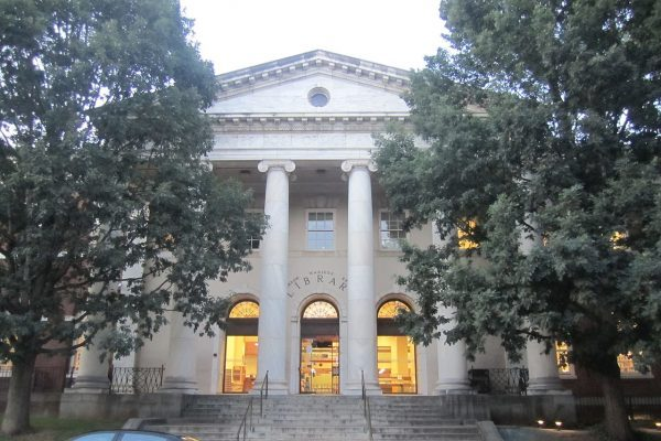 Charlottesville, VA insurance agency, nearby city library street view at dusk, limestone columned building.