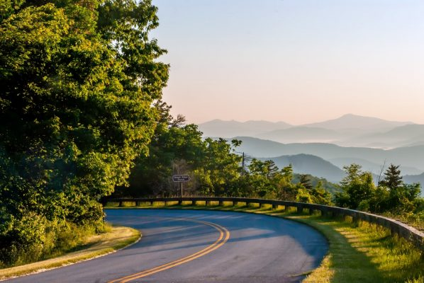 Asheville, NC Insurance Agency, a curve on the Blue Ridge Parkway overlooking scenic green mountains in the distance.