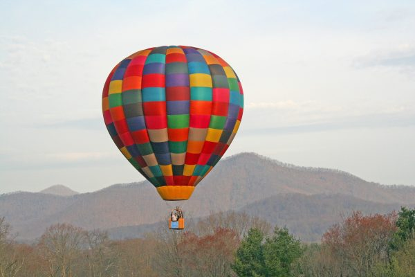 Asheville, NC Insurance Agency, colorful hot air balloon over Appalachian mountains in winter.