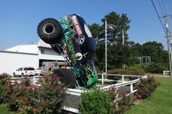 Elizabeth City, NC, monster truck graveyard, Digger's Dungeon, large green truck nosed into the ground before white metal building.