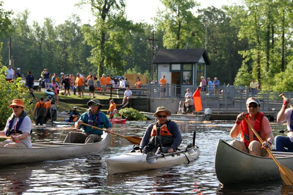 Elizabeth City, NC Great Dismal Swamp State Park, flotilla of canoes and kayaks on waterway, brightly colored paddlers.