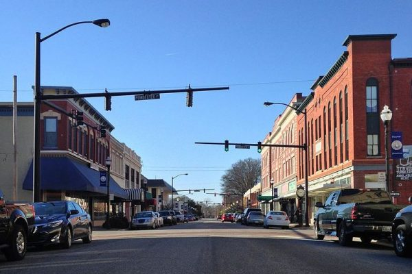 Elizabeth City, NC, street view of downtown shops, multi-storied red brick buildings with awnings covering sidewalks.
