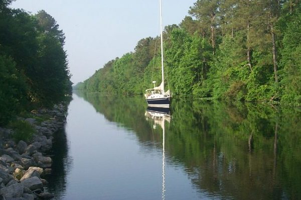 Elizabeth City, NC blue and white sailboat on intracoastal waterway canal.